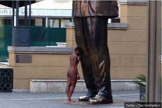 Donna nuda sotto la statua di Nelson Mandela