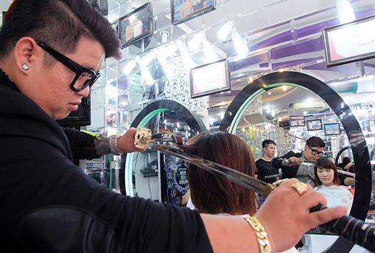 Nguyen Hoang Hung parrucchiere per il taglio capelli utilizza la spada del Samurai
