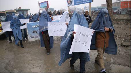 Attivisti uomini in burqa sfilano per i diritti delle donne in Afghanistan